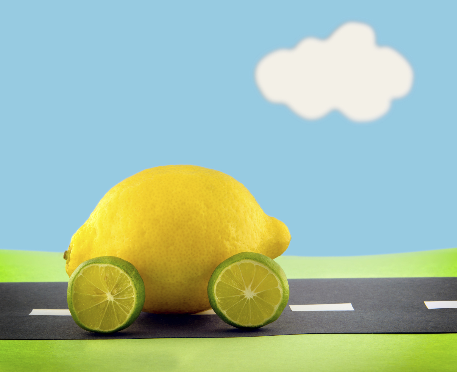 A lemon car with lime wheels driving along a construction paper scene.  Scene made by the photographer.