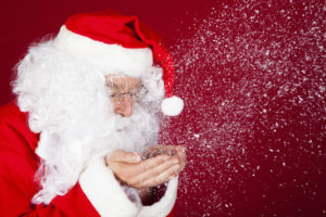 Portrait of santa blowing snow over red background