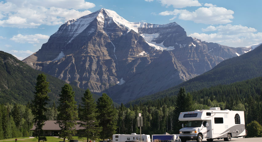 RV parked in front of majestic mountains