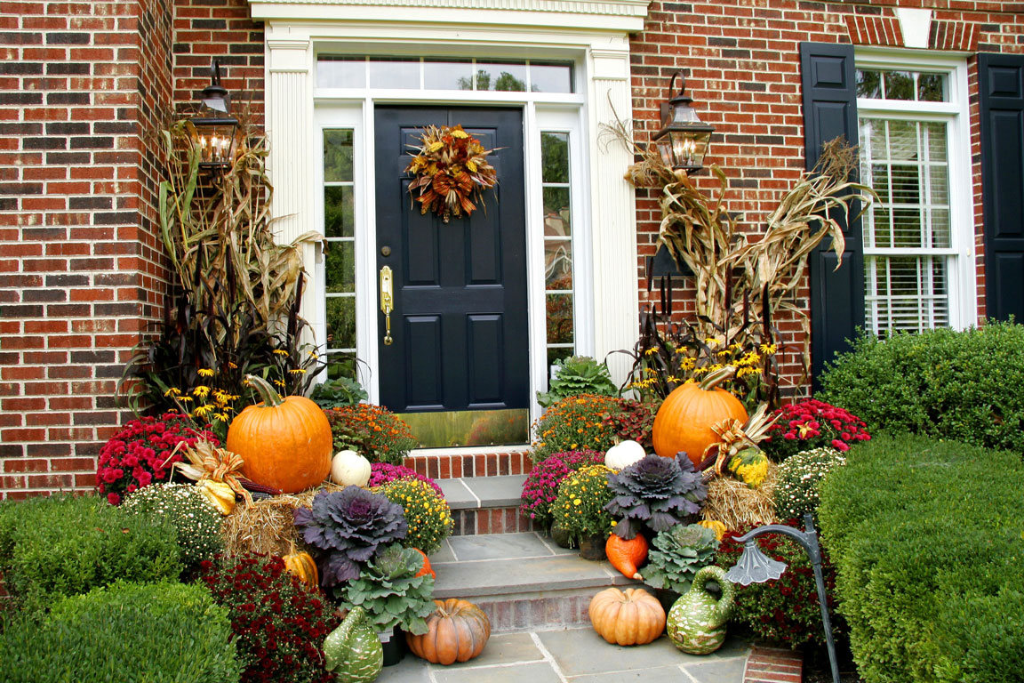 front door decorate for autum with a fallish wreath, pumpkins, squash, and corn stalks
